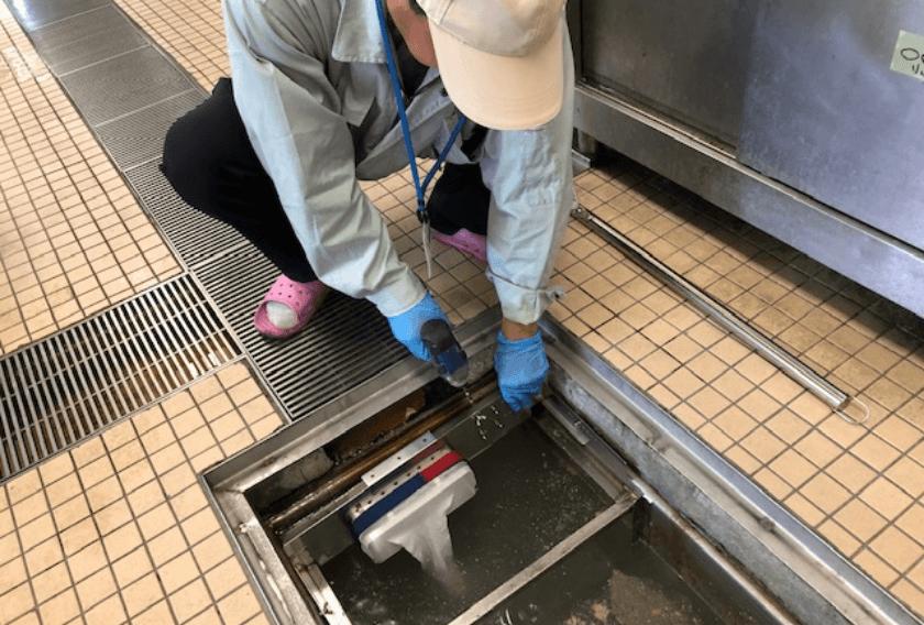 作業員が阻集器に機材を設置する写真