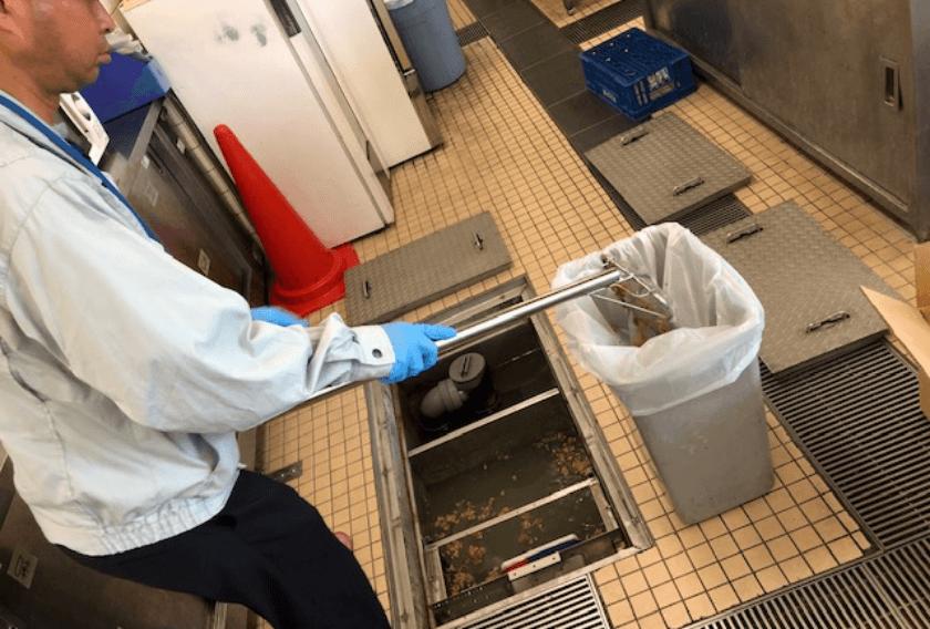 作業員が油脂吸着用資材にて吸着除去をする写真